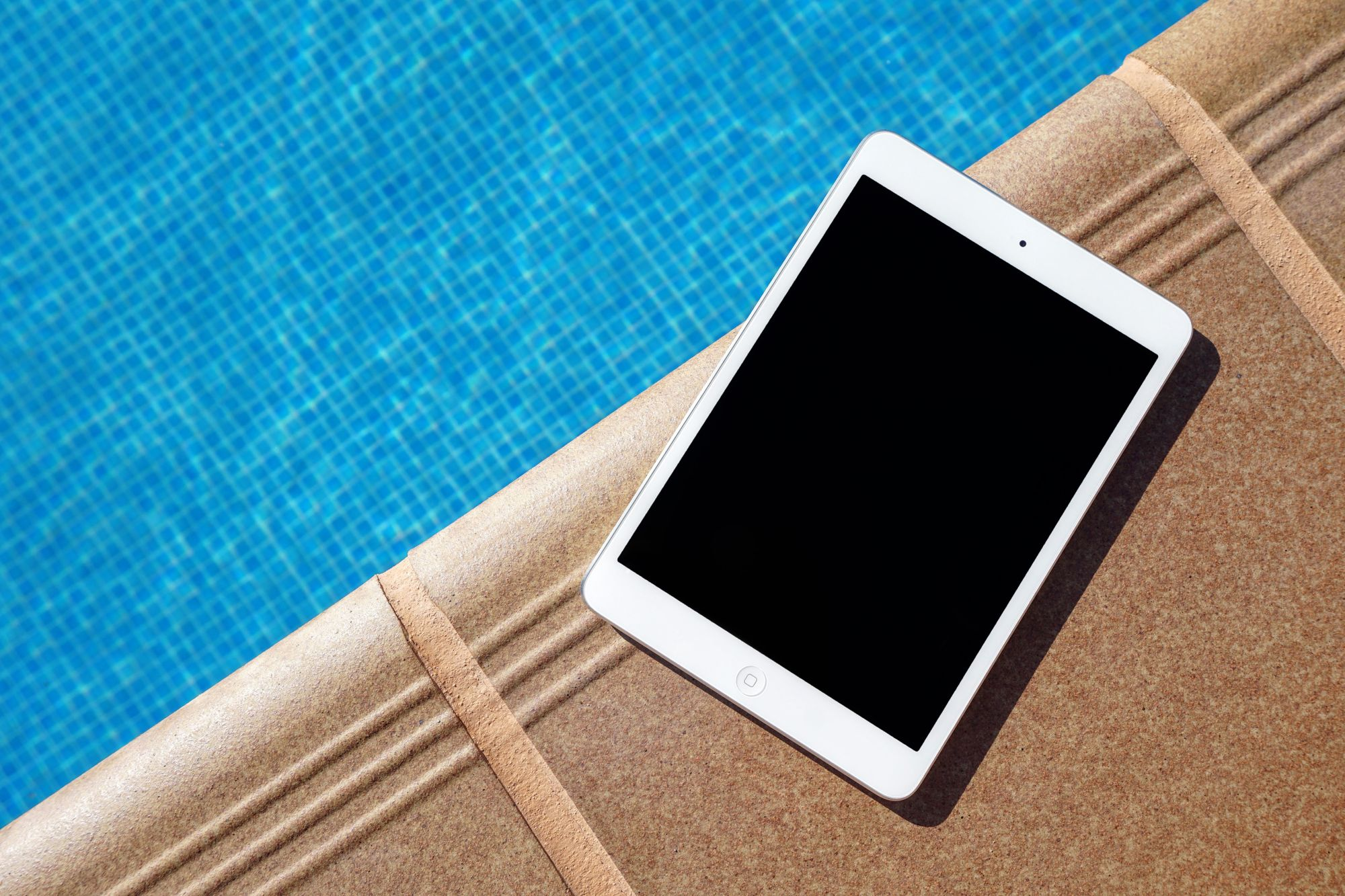 An iPad placed on the edge of a swimming pool