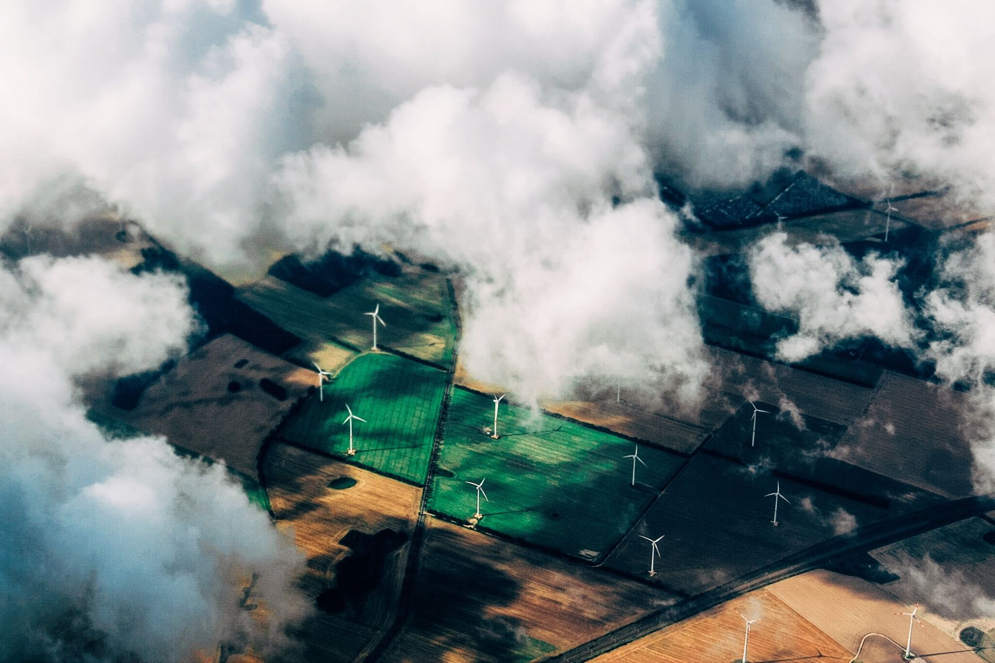 An aerial shot of wind turbines in fields, with fluffy clouds obscuring some of the view